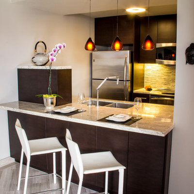 Example of a small trendy galley medium tone wood floor and brown floor open concept kitchen design in Hawaii with an undermount sink, flat-panel cabinets, dark wood cabinets, granite countertops, green backsplash, glass tile backsplash, stainless steel appliances and a peninsula