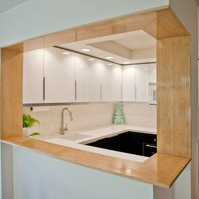 Kitchen - modern u-shaped kitchen idea in San Diego with flat-panel cabinets, white cabinets, white backsplash, subway tile backsplash and black appliances