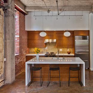 サンフランシスコのインダストリアルスタイルのおしゃれなII型キッチン (一体型シンク、シルバーの調理設備、フラットパネル扉のキャビネット、中間色木目調キャビネット、クオーツストーンカウンター) の写真