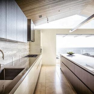 Immagine di una cucina moderna di medie dimensioni con lavello sottopiano, ante lisce, ante in legno bruno, top in zinco, paraspruzzi marrone, paraspruzzi con piastrelle in pietra, elettrodomestici in acciaio inossidabile, pavimento in travertino e isola