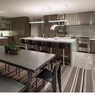 Modelo de cocina comedor en U, moderna, grande, con fregadero bajoencimera, armarios con paneles lisos, puertas de armario marrones, salpicadero blanco, electrodomésticos de acero inoxidable, suelo laminado, una isla, suelo gris y encimeras blancas