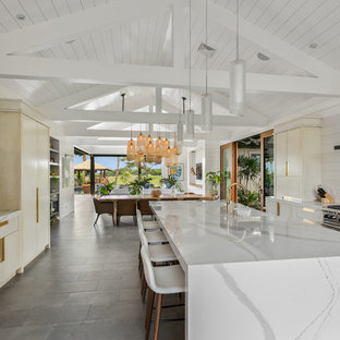 Large beach style galley open plan kitchen in Hawaii with a farmhouse sink, flat-panel cabinets, white cabinets, quartz benchtops, white splashback, stone slab splashback, stainless steel appliances, ceramic floors, with island and grey floor.