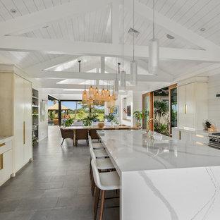 ハワイの広いビーチスタイルのおしゃれなキッチン (エプロンフロントシンク、フラットパネル扉のキャビネット、白いキャビネット、クオーツストーンカウンター、白いキッチンパネル、石スラブのキッチンパネル、シルバーの調理設備、セラミックタイルの床、グレーの床) の写真