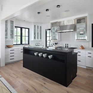 Country open plan kitchen in Milwaukee with glass-front cabinets, stainless steel cabinets, white splashback, stainless steel appliances, light hardwood floors, with island and grey benchtop.