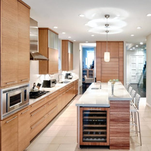 Large contemporary galley kitchen/diner in Chicago with flat-panel cabinets, light wood cabinets, white splashback, metro tiled splashback, integrated appliances, an island, a submerged sink, composite countertops and ceramic flooring.