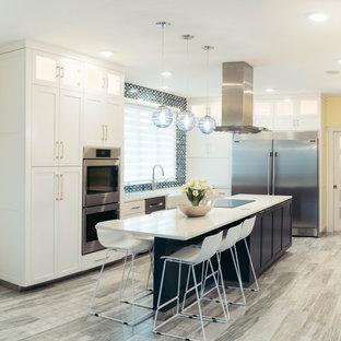他の地域の大きいモダンスタイルのおしゃれなキッチン (エプロンフロントシンク、シェーカースタイル扉のキャビネット、黄色いキャビネット、クオーツストーンカウンター、青いキッチンパネル、ガラスタイルのキッチンパネル、シルバーの調理設備の、磁器タイルの床、グレーの床、白いキッチンカウンター) の写真