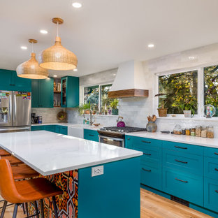 Inspiration for a mid-sized eclectic l-shaped eat-in kitchen in Other with shaker cabinets, blue cabinets, quartz benchtops, white splashback, ceramic splashback, stainless steel appliances, vinyl floors, with island, white benchtop, a farmhouse sink and brown floor.
