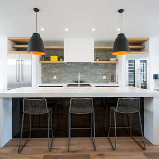 Contemporary open concept kitchen remodeling - Inspiration for a contemporary galley light wood floor and beige floor open concept kitchen remodel in New York with stainless steel cabinets, gray backsplash, stone slab backsplash, stainless steel appliances and an island