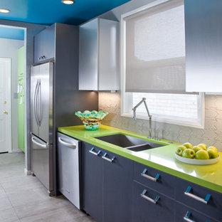他の地域の中サイズのコンテンポラリースタイルのおしゃれなキッチン (アンダーカウンターシンク、フラットパネル扉のキャビネット、ステンレスキャビネット、クオーツストーンカウンター、グレーのキッチンパネル、セラミックタイルのキッチンパネル、シルバーの調理設備の、磁器タイルの床、アイランドなし、緑のキッチンカウンター) の写真