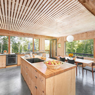 Rustic eat-in kitchen appliance - Example of a mountain style concrete floor eat-in kitchen design in Portland Maine with flat-panel cabinets, light wood cabinets, wood countertops, window backsplash, stainless steel appliances and an island