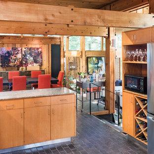 Inspiration för mellanstora moderna grått kök, med släta luckor, skåp i mellenmörkt trä, granitbänkskiva, grått stänkskydd, stänkskydd i sten, rostfria vitvaror, en köksö, en dubbel diskho, tegelgolv och svart golv