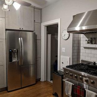 オマハの小さいシャビーシック調のおしゃれなキッチン (エプロンフロントシンク、シェーカースタイル扉のキャビネット、グレーのキャビネット、クオーツストーンカウンター、白いキッチンパネル、磁器タイルのキッチンパネル、シルバーの調理設備の、無垢フローリング、茶色い床、白いキッチンカウンター) の写真