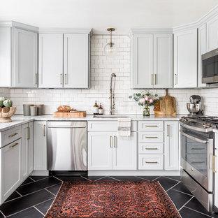 Idéer för vintage u-kök, med en undermonterad diskho, skåp i shakerstil, grå skåp, vitt stänkskydd, stänkskydd i tunnelbanekakel, rostfria vitvaror och svart golv