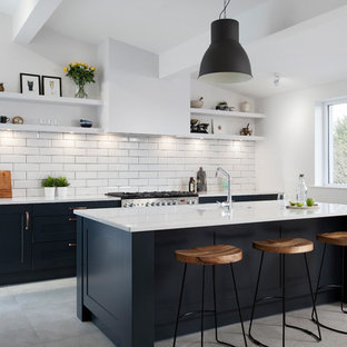 Classic galley kitchen in Belfast with a single-bowl sink, stainless steel appliances, an island, shaker cabinets, blue cabinets, white splashback, metro tiled splashback, grey floors and white worktops.