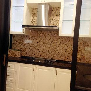 他の地域の小さいヴィクトリアン調のおしゃれなキッチン (アンダーカウンターシンク、インセット扉のキャビネット、ベージュのキャビネット、人工大理石カウンター、茶色いキッチンパネル、モザイクタイルのキッチンパネル、黒い調理設備、磁器タイルの床) の写真
