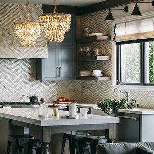 Klassisk inredning av ett mellanstort vit vitt kök, med en rustik diskho, skåp i shakerstil, grå skåp, bänkskiva i kvarts, vitt stänkskydd, rostfria vitvaror, en köksö, svart golv och stänkskydd i marmor