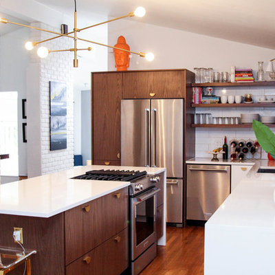 Inspiration for a mid-sized mid-century modern l-shaped medium tone wood floor and brown floor enclosed kitchen remodel in Cincinnati with an undermount sink, flat-panel cabinets, dark wood cabinets, white backsplash, ceramic backsplash, stainless steel appliances, an island and white countertops