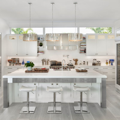 Example of a beach style u-shaped light wood floor and gray floor kitchen design in Miami with a farmhouse sink, white cabinets, white backsplash, stainless steel appliances, an island and shaker cabinets