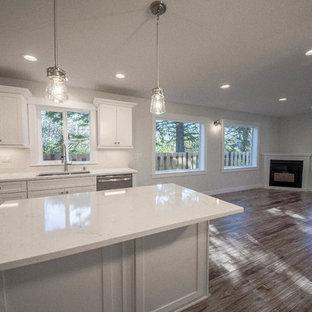 Offene Maritime Küche mit Laminat, braunem Boden, Doppelwaschbecken, Schrankfronten im Shaker-Stil, weißen Schränken, Quarzwerkstein-Arbeitsplatte, Küchenrückwand in Weiß, bunten Elektrogeräten und Kücheninsel in Seattle