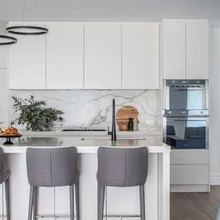 This is an example of a contemporary l-shaped kitchen in Sydney with an undermount sink, quartz benchtops, ceramic splashback, stainless steel appliances, medium hardwood floors, white benchtop, flat-panel cabinets, white cabinets, white splashback, with island and brown floor.