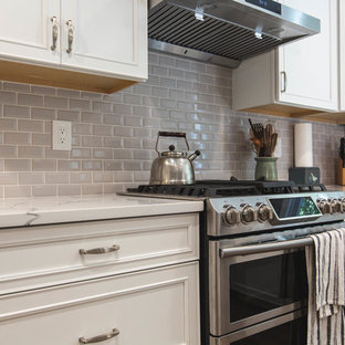 Large contemporary u-shaped open plan kitchen in DC Metro with an undermount sink, raised-panel cabinets, white cabinets, quartz benchtops, grey splashback, subway tile splashback, stainless steel appliances, vinyl floors, with island, brown floor and white benchtop.