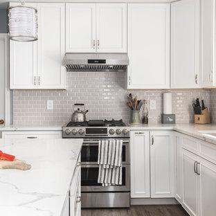 Bild på ett stort funkis vit vitt kök, med en undermonterad diskho, luckor med upphöjd panel, vita skåp, bänkskiva i kvarts, grått stänkskydd, stänkskydd i tunnelbanekakel, rostfria vitvaror, vinylgolv, en köksö och brunt golv