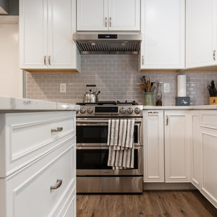 This is an example of a large contemporary u-shaped open plan kitchen in DC Metro with an undermount sink, raised-panel cabinets, white cabinets, quartz benchtops, grey splashback, subway tile splashback, stainless steel appliances, vinyl floors, with island, brown floor and white benchtop.
