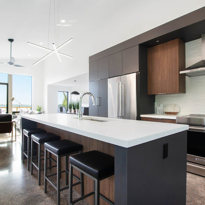 Large minimalist concrete floor and brown floor open concept kitchen photo in Grand Rapids with an undermount sink, flat-panel cabinets, dark wood cabinets, quartz countertops, white backsplash, stainless steel appliances, an island and white countertops