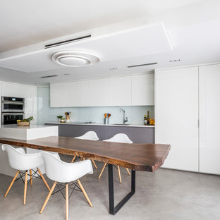 Mid-sized contemporary eat-in kitchen appliance - Inspiration for a mid-sized contemporary l-shaped concrete floor eat-in kitchen remodel in Miami with an undermount sink, flat-panel cabinets, white cabinets, quartz countertops, white backsplash, glass sheet backsplash, paneled appliances and an island