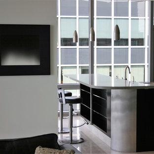 Diseño de cocina en L, moderna, grande, abierta, con una isla, fregadero bajoencimera, armarios con paneles lisos, puertas de armario negras, encimera de acrílico, salpicadero de piedra caliza, electrodomésticos de acero inoxidable, suelo de piedra caliza y suelo beige
