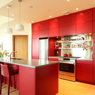 Example of a small minimalist medium tone wood floor open concept kitchen design in Other with an undermount sink, flat-panel cabinets, red cabinets, solid surface countertops, metal backsplash, stainless steel appliances and an island