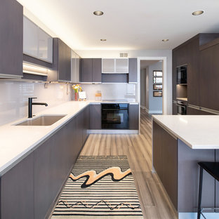 Photo of a large modern open plan kitchen in Kansas City with an integrated sink, glass-front cabinets, dark wood cabinets, quartz benchtops, glass sheet splashback, panelled appliances and a peninsula.