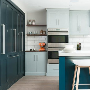 Inspiration for a large contemporary single-wall open plan kitchen in Kent with a built-in sink, recessed-panel cabinets, blue cabinets, composite countertops, white splashback, ceramic splashback, stainless steel appliances, light hardwood flooring and an island.