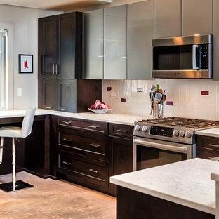 Cette image montre une cuisine américaine traditionnelle en U de taille moyenne avec un plan de travail en quartz modifié, une crédence multicolore, une crédence en carreau de céramique, un électroménager en acier inoxydable, un sol en carrelage de céramique, une péninsule, un évier de ferme, un placard à porte plane, des portes de placard grises, un sol beige et un plan de travail gris.