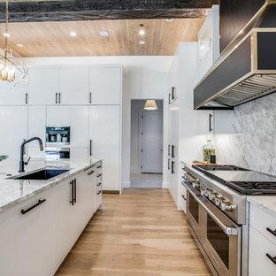 ダラスの広い地中海スタイルのおしゃれなキッチン (ドロップインシンク、フラットパネル扉のキャビネット、白いキャビネット、大理石カウンター、白いキッチンパネル、大理石のキッチンパネル、シルバーの調理設備、淡色無垢フローリング、茶色い床、白いキッチンカウンター) の写真