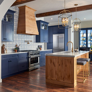 This is an example of a large beach style galley eat-in kitchen in San Diego with an undermount sink, shaker cabinets, blue cabinets, solid surface benchtops, blue splashback, porcelain splashback, stainless steel appliances, with island, brown floor, grey benchtop and dark hardwood floors.