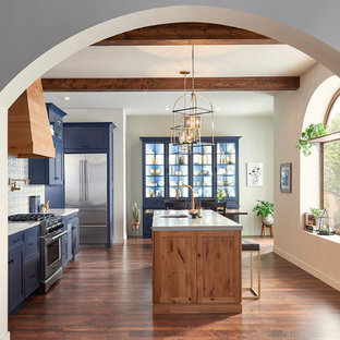 Example of a large tuscan single-wall brown floor eat-in kitchen design in San Diego with an undermount sink, shaker cabinets, blue cabinets, solid surface countertops, blue backsplash, porcelain backsplash, stainless steel appliances, an island and gray countertops