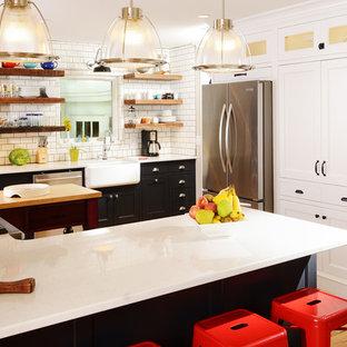 他の地域の中サイズのカントリー風おしゃれなキッチン (エプロンフロントシンク、シェーカースタイル扉のキャビネット、黒いキャビネット、白いキッチンパネル、サブウェイタイルのキッチンパネル、シルバーの調理設備の、淡色無垢フローリング、クオーツストーンカウンター、白いキッチンカウンター) の写真