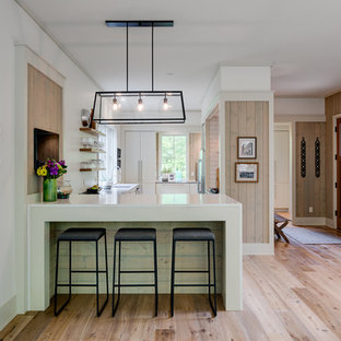 This is an example of a large modern u-shaped open plan kitchen in Other with an undermount sink, flat-panel cabinets, white cabinets, soapstone benchtops, beige splashback, ceramic splashback, stainless steel appliances, light hardwood floors, a peninsula and brown floor.