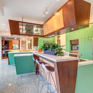 Modelo de cocina en L, vintage, abierta, con armarios con paneles lisos, encimera de cuarzo compacto, electrodomésticos de acero inoxidable, una isla y puertas de armario verdes