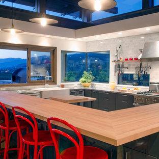 Idée de décoration pour une grande cuisine minimaliste en L avec un évier de ferme, un placard à porte plane, des portes de placard grises, un plan de travail en bois, un électroménager en acier inoxydable, une crédence grise, une crédence en carrelage de pierre, un sol en bois foncé et un îlot central.