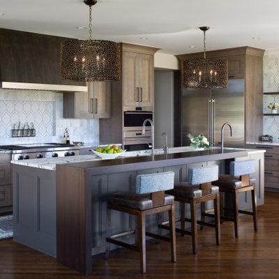 Large island style l-shaped medium tone wood floor and brown floor open concept kitchen photo in Denver with an undermount sink, recessed-panel cabinets, gray cabinets, white backsplash, marble backsplash, stainless steel appliances, an island, white countertops and marble countertops
