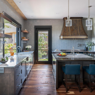 デンバーの大きいトラディショナルスタイルのおしゃれなキッチン (エプロンフロントシンク、シェーカースタイル扉のキャビネット、中間色木目調キャビネット、珪岩カウンター、青いキッチンパネル、磁器タイルのキッチンパネル、カラー調理設備、無垢フローリング、茶色い床、白いキッチンカウンター) の写真