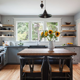 This is an example of a mid-sized arts and crafts l-shaped separate kitchen in San Francisco with a farmhouse sink, shaker cabinets, grey cabinets, white splashback, ceramic splashback, stainless steel appliances, light hardwood floors, with island, beige floor and soapstone benchtops.