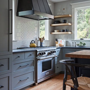 Inspiration for a medium sized classic l-shaped enclosed kitchen in San Francisco with a belfast sink, shaker cabinets, grey cabinets, soapstone worktops, white splashback, ceramic splashback, stainless steel appliances, light hardwood flooring, an island and beige floors.
