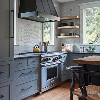 Example of a mid-sized arts and crafts l-shaped light wood floor and beige floor enclosed kitchen design in San Francisco with a farmhouse sink, shaker cabinets, gray cabinets, soapstone countertops, white backsplash, ceramic backsplash, stainless steel appliances and an island