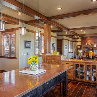 Idée de décoration pour une cuisine craftsman en U avec un placard à porte shaker, des portes de placard en bois brun, un plan de travail en cuivre, un sol en bois foncé, un îlot central et un sol marron.