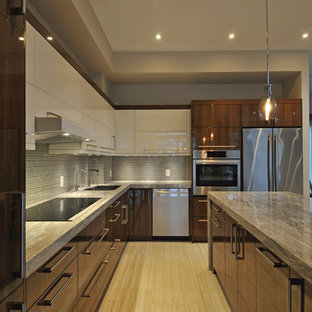 Photo of a mid-sized contemporary l-shaped eat-in kitchen in Toronto with an undermount sink, flat-panel cabinets, white cabinets, limestone benchtops, grey splashback, ceramic splashback, stainless steel appliances, dark hardwood floors, with island, brown floor and brown benchtop.