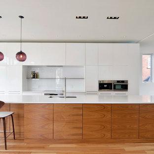 Immagine di una cucina moderna con lavello sottopiano, ante lisce, ante bianche, paraspruzzi bianco e elettrodomestici in acciaio inossidabile