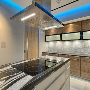 ロサンゼルスの大きいコンテンポラリースタイルのおしゃれなキッチン (シングルシンク、フラットパネル扉のキャビネット、中間色木目調キャビネット、オニキスカウンター、グレーのキッチンパネル、セラミックタイルのキッチンパネル、白い調理設備、セラミックタイルの床、白い床) の写真